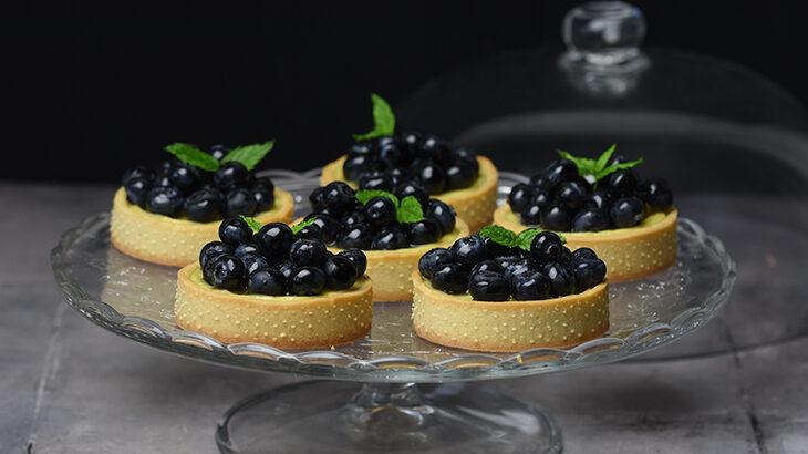 cheesecake med blåbær - bagt cheesecake med citron som små tærter toppet med blåbær